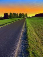 Country road into surreal sundown by patrickjobst