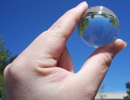Hand holding glass ball by Stock-by-Kai