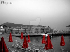 red umbrellas on the beach by AleksandarN