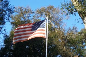 US Flag on pole in wind by paintresseye