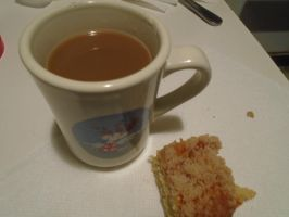A cup of coffee and a slice of coffee cake by mylesterlucky7