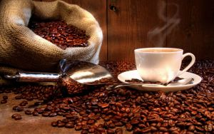 Hot Coffee Cup on Plate Over Roasted Coffee Beans by ProPhotoStock