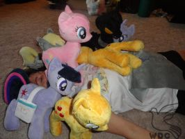 WhiteDove sleeping in a pile of ponies by WhiteDove-Creations